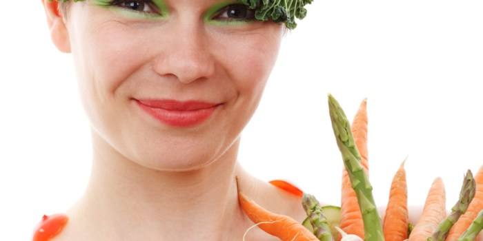 image of woman holding vegetables and wearing cabbage leaves on her head