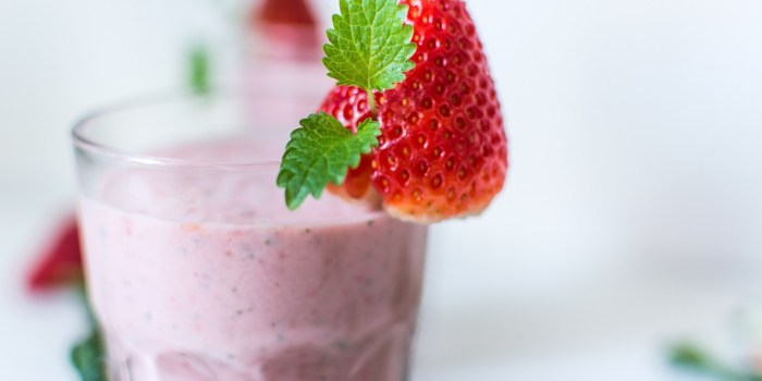 Image of glass holding Berry Blast smoothie by Intentionally Eat. The glass has a strawberry on the lip. Image for 5 healthy non-dairy smoothies by intentionally eat