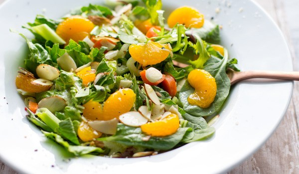 Easy Mandarin Salad Recipe by Intentionally Eat with Cindy Newland in a white bowl with a bronze spoon