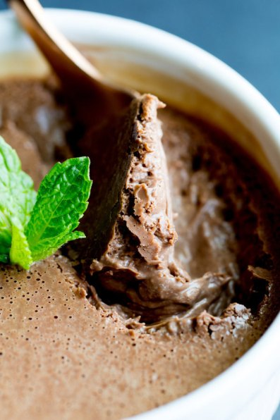 image of Mint Chocolate Pots de Creme by Cindy Newland with Intentionally Eat in a white bowl with a spoon and a mint leaf