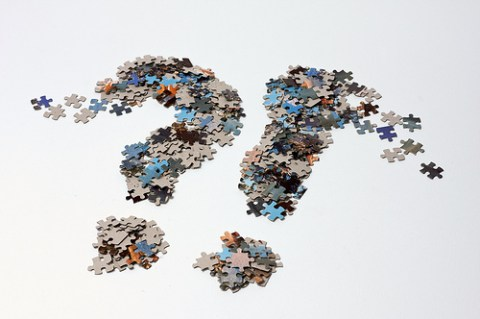 A question mark and an exclamation mark made from jigsaw puzzle pieces, next to each other, dissolving on the white background.