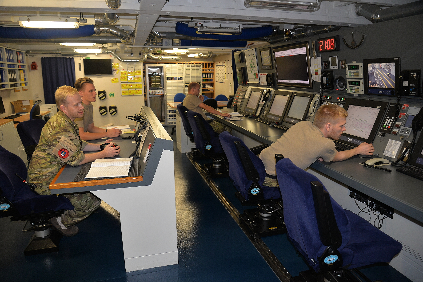 Electro Officer Christian Jens, in the foreground at left, oversees operations in the ship's Engineering Control center. With a crew of only 117, the Nils Juel relies on a high degree of automation. Fifty cameras monitor key spaces around the ship -- at right, one of them shows a view of the helicopter hangar.