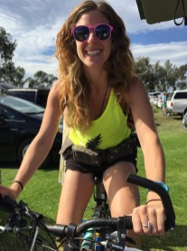 Lizzy wearing one of our bolt tanks riding a bike that powers a generator, making margaritas in the parking lot for us