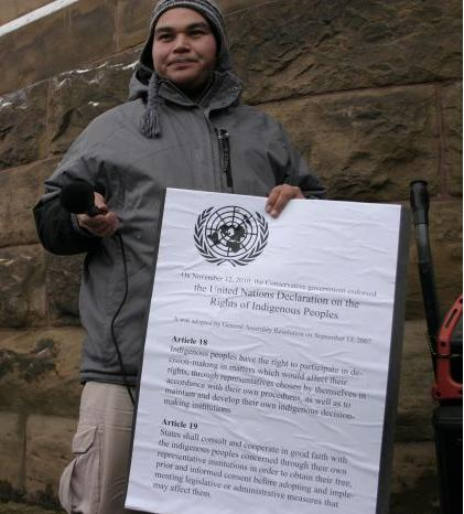 Norman Matchewan,  holding a copy of the UN Declaration on the Rights of Indigenous Peoples, Dec 2010. Photo Barriere Lake Solidarity