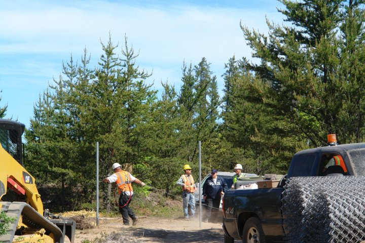 Kennecott employees placing a fence across the driveway to the Eagle Rock encampment with state police and mine security looking on. Photo by Greg Peterson