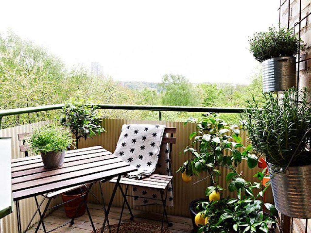 balkon rumah sebagai area privat dengan tanaman dan kursi