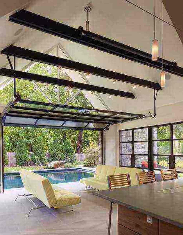 instalasi pintu garasi kaca yang menghubungkan area dalam rumah dan area kolam