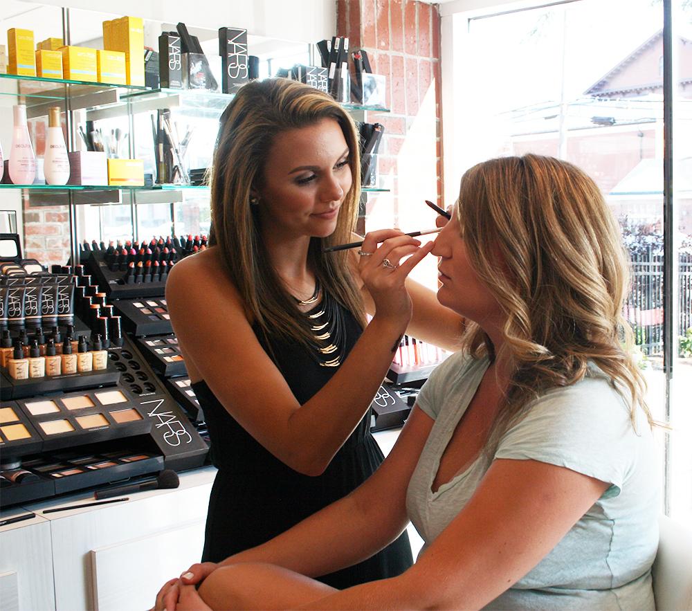 Noelle applying makeup during INTERLOCKS Effortless Summer hair and makeup event