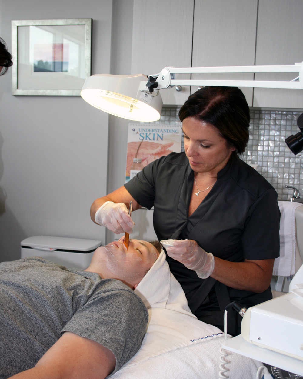 Master Aesthetician Debra applying product on facial client