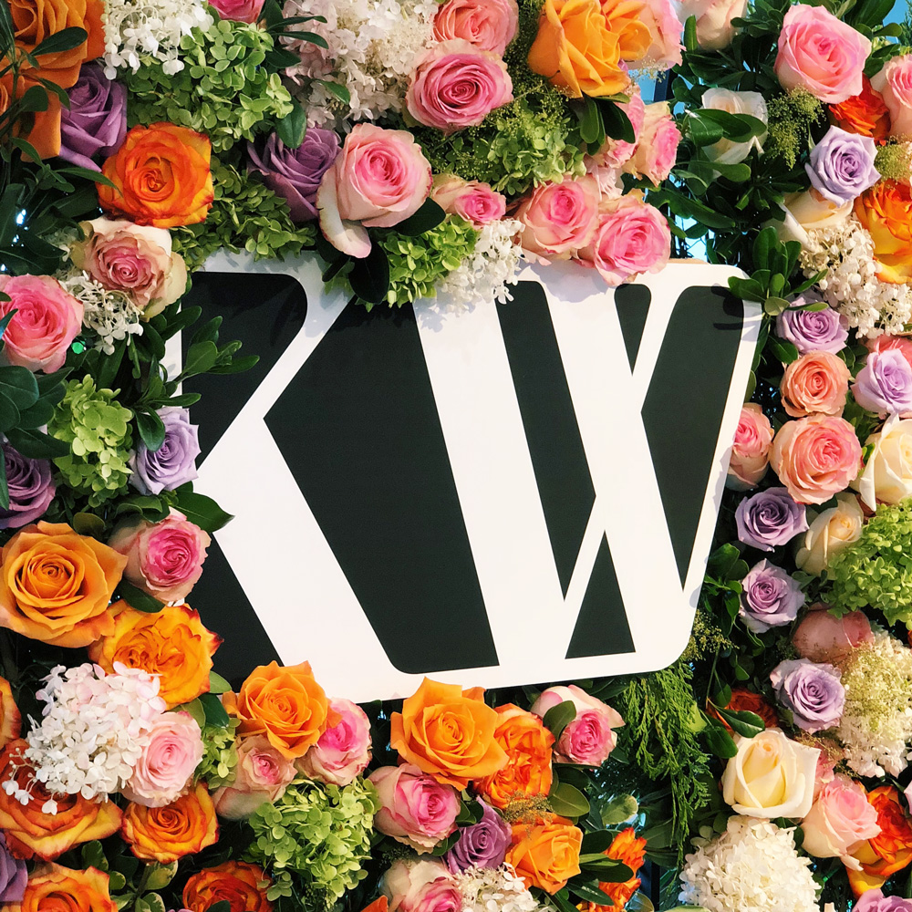 Kjaer Weis logo on flower wall at the INTERLOCKS Kjaer Weis Launch Party