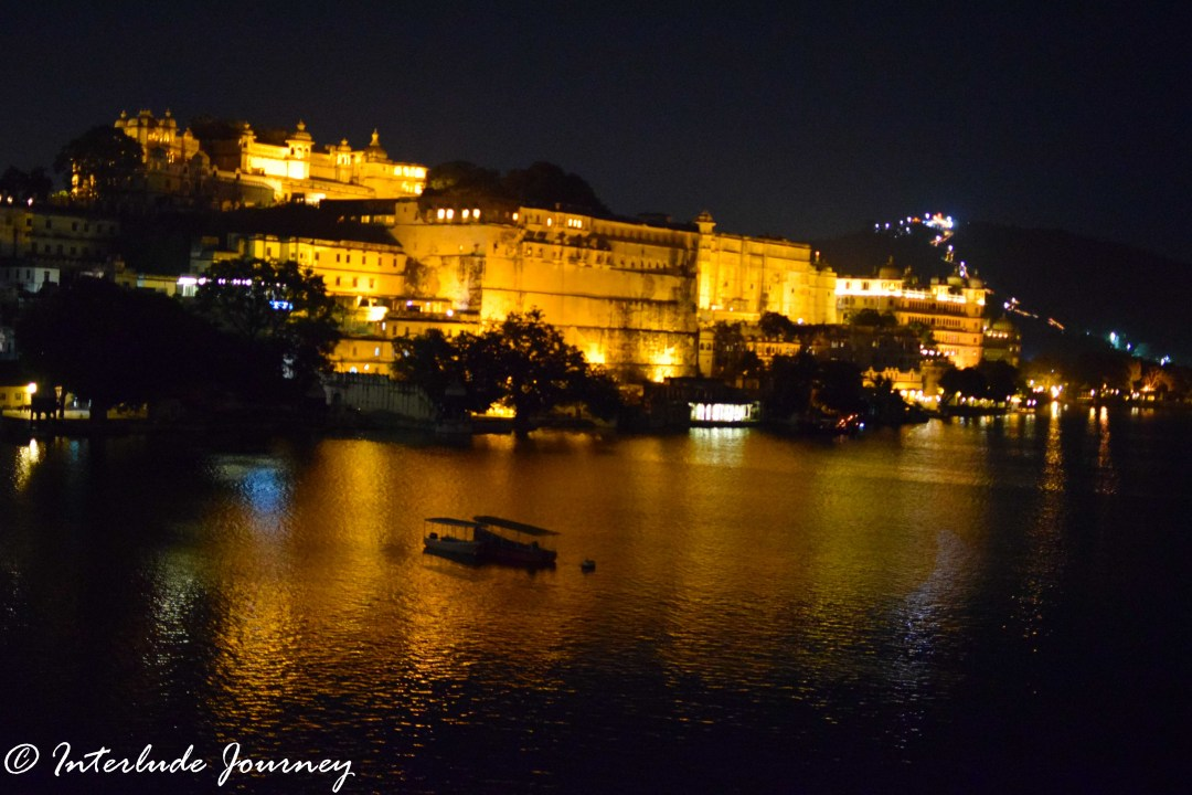 The magical view of illuminated City Palace of Udaipur and its reflection in Lake Pichola