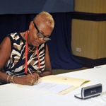 Margaret Sivers signing the Multilateral Competent Authority Agreement