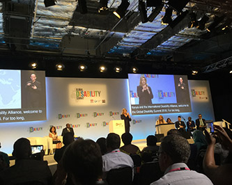 A photo shot from the audience of the first-ever global disability summit. Speakers present onstage .