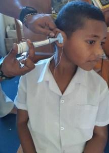 A Fijian boy has an ear mold made by an audiologist.