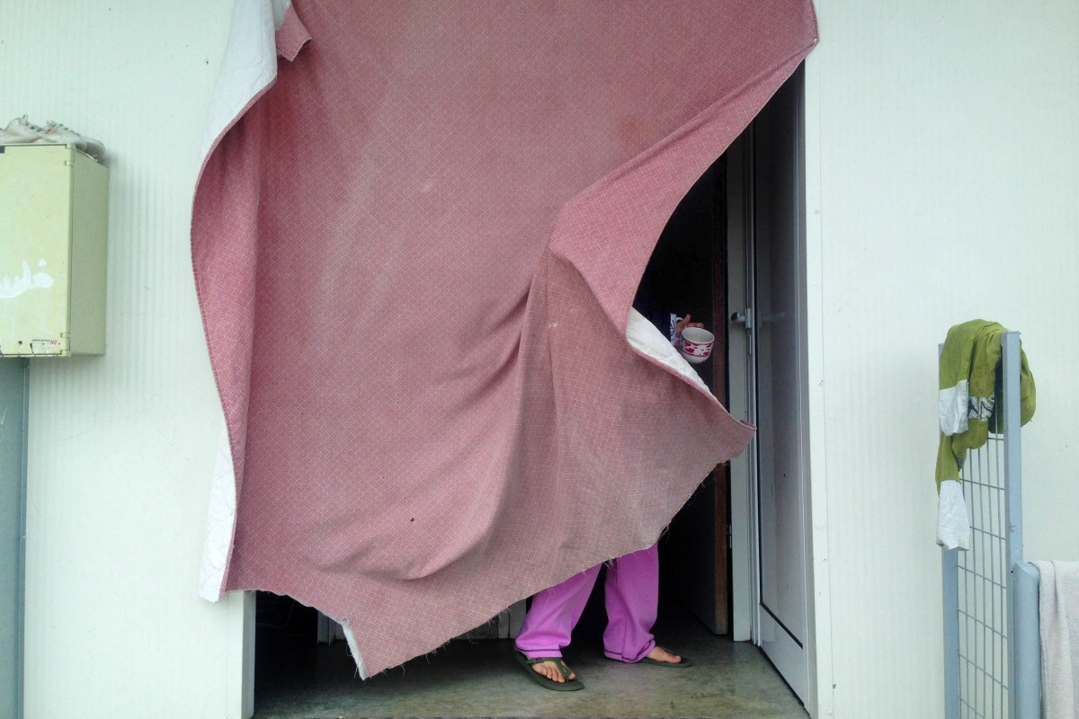 A Syrian refugee pushes the curtain that acts as a door to her living space at the Kofinou refugee camp in Cyprus.