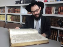 PHOTO/Dave Soboro Rabbi Shmuel Kot, chief Rabbi of Estonia, flips through the old religious books at the Estonian Jewish Center.