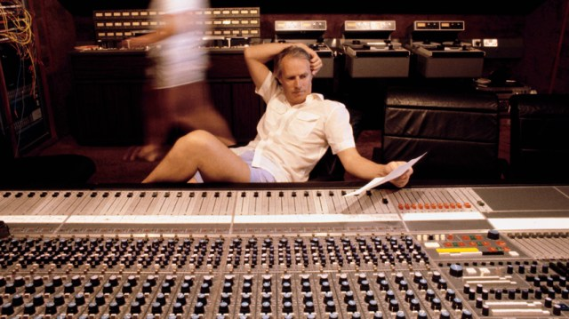 1980s --- Prominent recording producer George Martin sits in a studio next to a sound board. Martin is best known for his work with the Beatles. --- Image by © Martyn Goddard/CORBIS