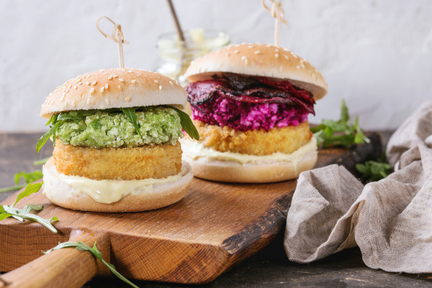 vegetarian Tahini and Quinoa burger topped with green goddess sauce and avocado & cabbage coleslaw