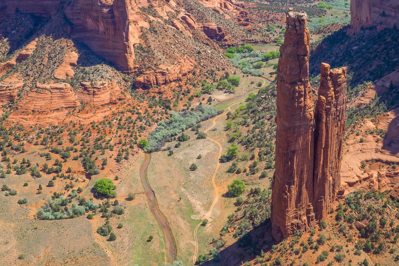 """Spider Rock is an 800-foot sandstone spire that rises from the canyon floor at the junction of Canyon de Chelly and Monument Canyon. From the overlook you can see the volcanic core of Black Rock Butte and the Chuska Mountains on the horizon. Traditional stories of the Diné elders tell of the """"Spider Woman"""" who wove her web of the universe and taught Diné to create beauty in their own life and spread the """"Beauty Way"""" teaching of balance within the mind, body, and soul."""