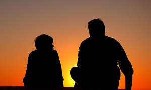 Vater und Sohn im Sonnenuntergang im Gespräch
