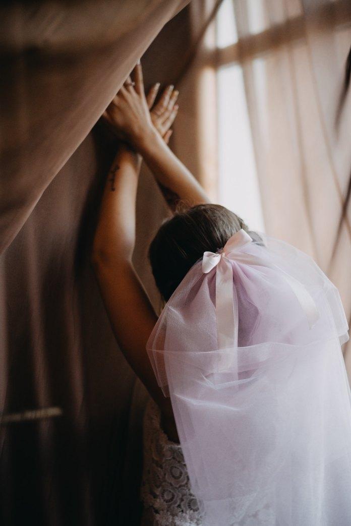 A bride with hands reaching upward