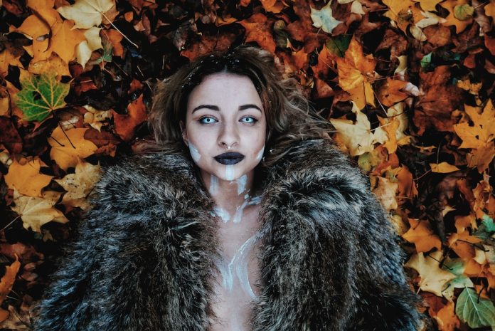 A girl wearing fur and no top laying on a bed of leaves also wearing albino lenses
