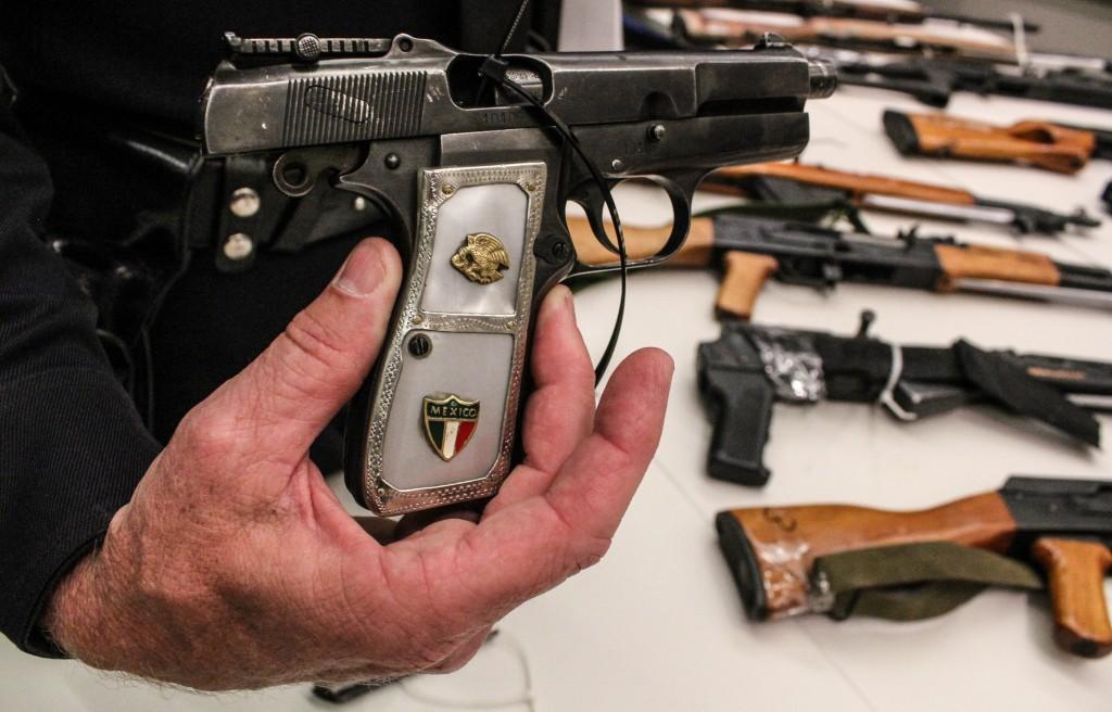 Commander Andrew Smith holds a 9mm handgun.   Daina Beth Solomon