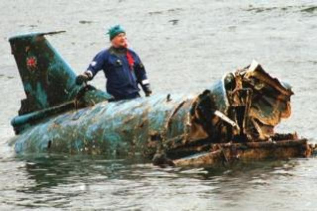 Bill Smith with the wreckage of Bluebird, which had been lifted from Coniston Water in 2001