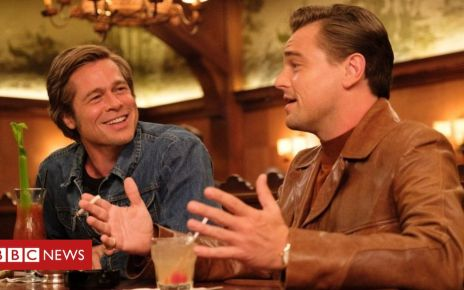 107064917 once upon a time in hollywood 2019 002 leonardo dicaprio brad pitt laughing talking in bar - Once Upon a Time in Hollywood: Exploring Tarantino's return