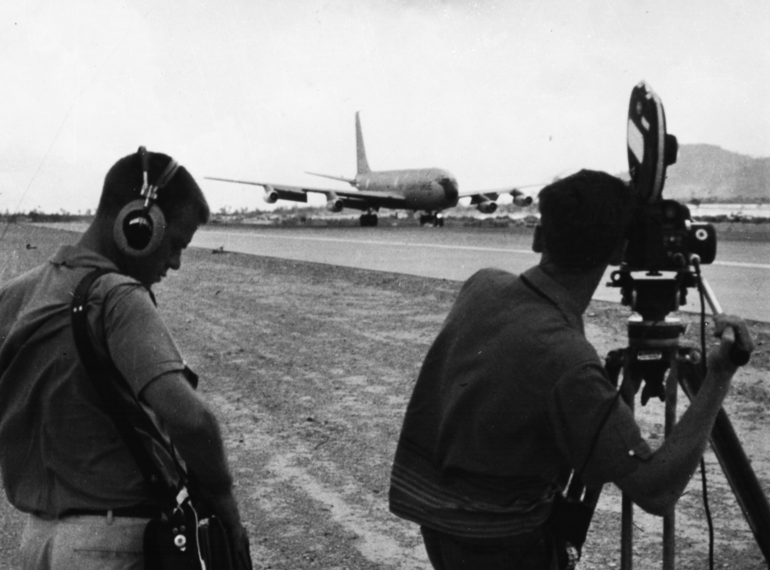 Two men stand at the end of a runway