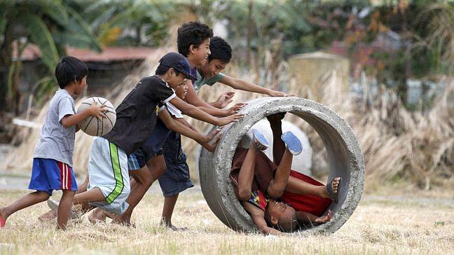 Meninos brincam com cano usado para controle de enchentes em Las Pinas, Manila (Foto: Erik de Castro / Reuters)