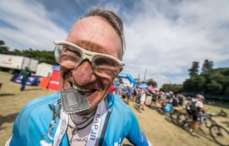 A rider bites his medal after finishing day three of sani2c Adventure