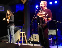 Bruce Daigrepont belts out a Cajun tune while fiddle player Gina Forsyth plays along.