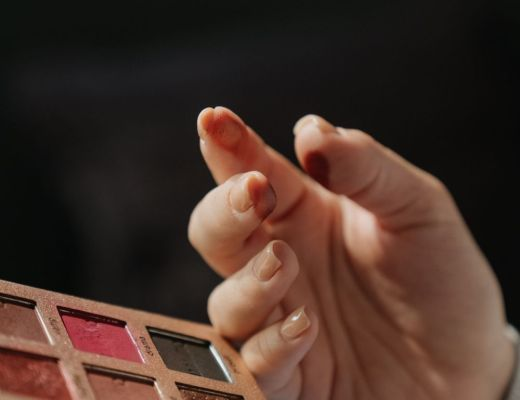 Hand next to makeup palette