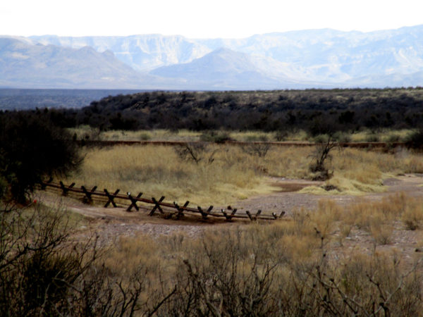 Fence in the foreground and mountains in the background