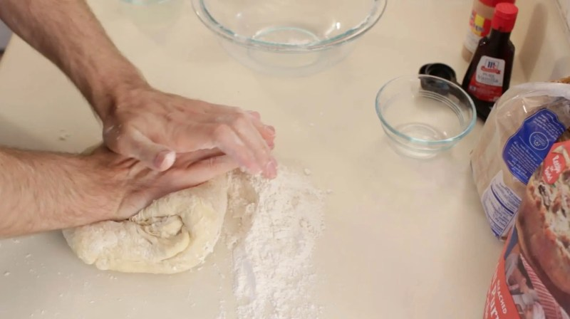 Hands kneading dough on a counter top with flour.