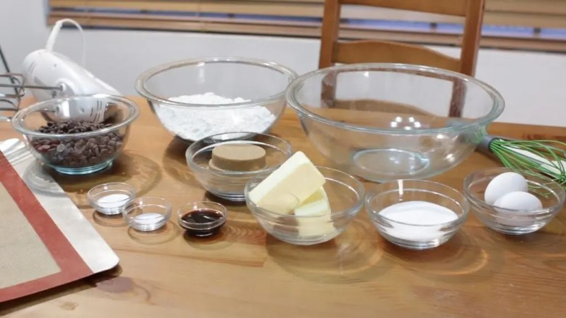 An assortment of large and small glass bowls sitting on a wooden table holding various chocolate chip cookie ingredients.