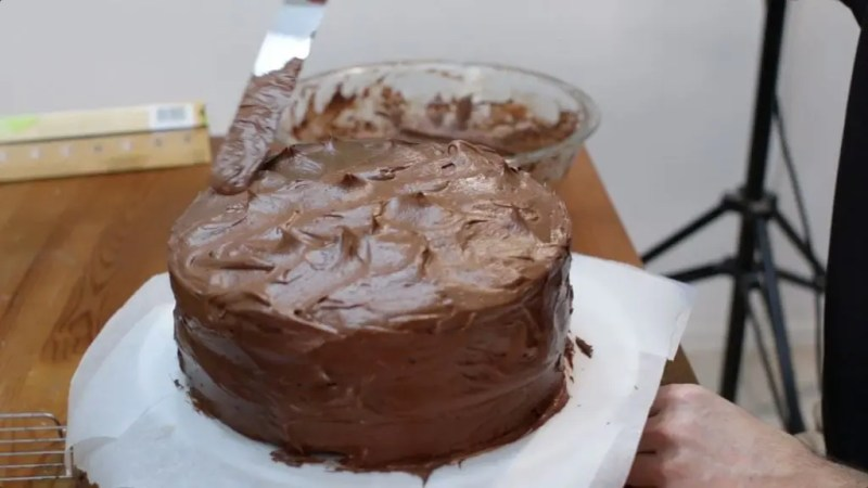 Chocolate cake covered with chocolate buttercream frosting sitting on a parchment paper lined cake stand.