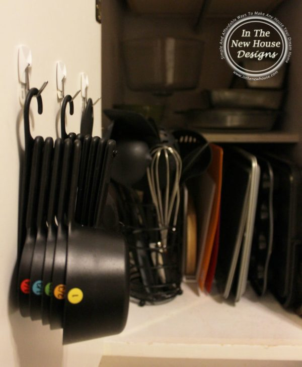 Hang measuring cups and spoons on a cabinet door for easy access