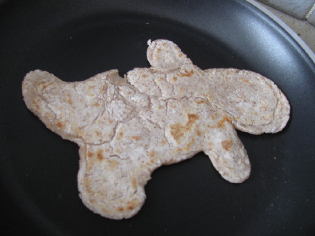 cooked gingerbread man shaped roti in the pan