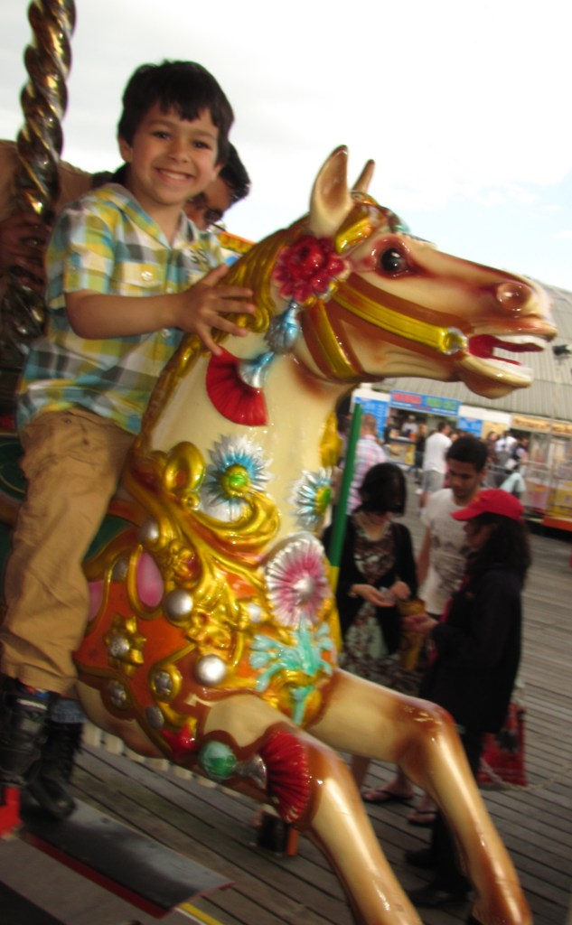 little boy on fairground horse merry-go-round merrygoround merry go round ride