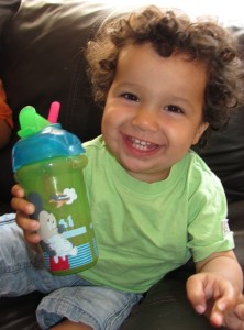 curly haired grinning smiling little boy toddler in a green tshirt with a beaker of chocolate milk with a straw
