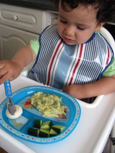 toddler boy in a high chair wearing a blue stripey bib eating dinner from a plate with different sections in it compartment plate eating cucumber cheese and pasta