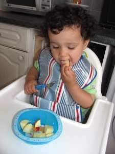 toddler boy in a high chair wearing a blue stripey bib eating a snack of apples from a winnie the pooh bowl