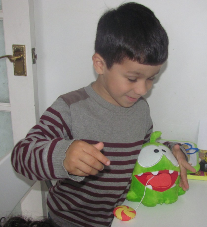 boy playing with om nom candy monster