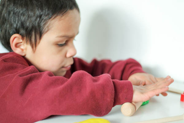 using a rolling pin with playdough