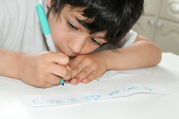 child writing shahada in arabic