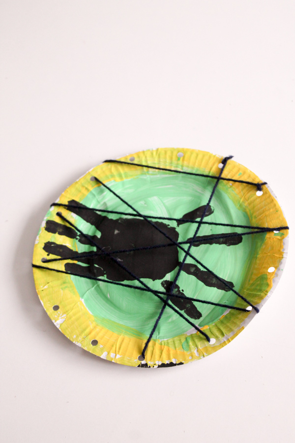 Spider and web paper plate handprint craft with wool. Great for halloween or mini beast theme