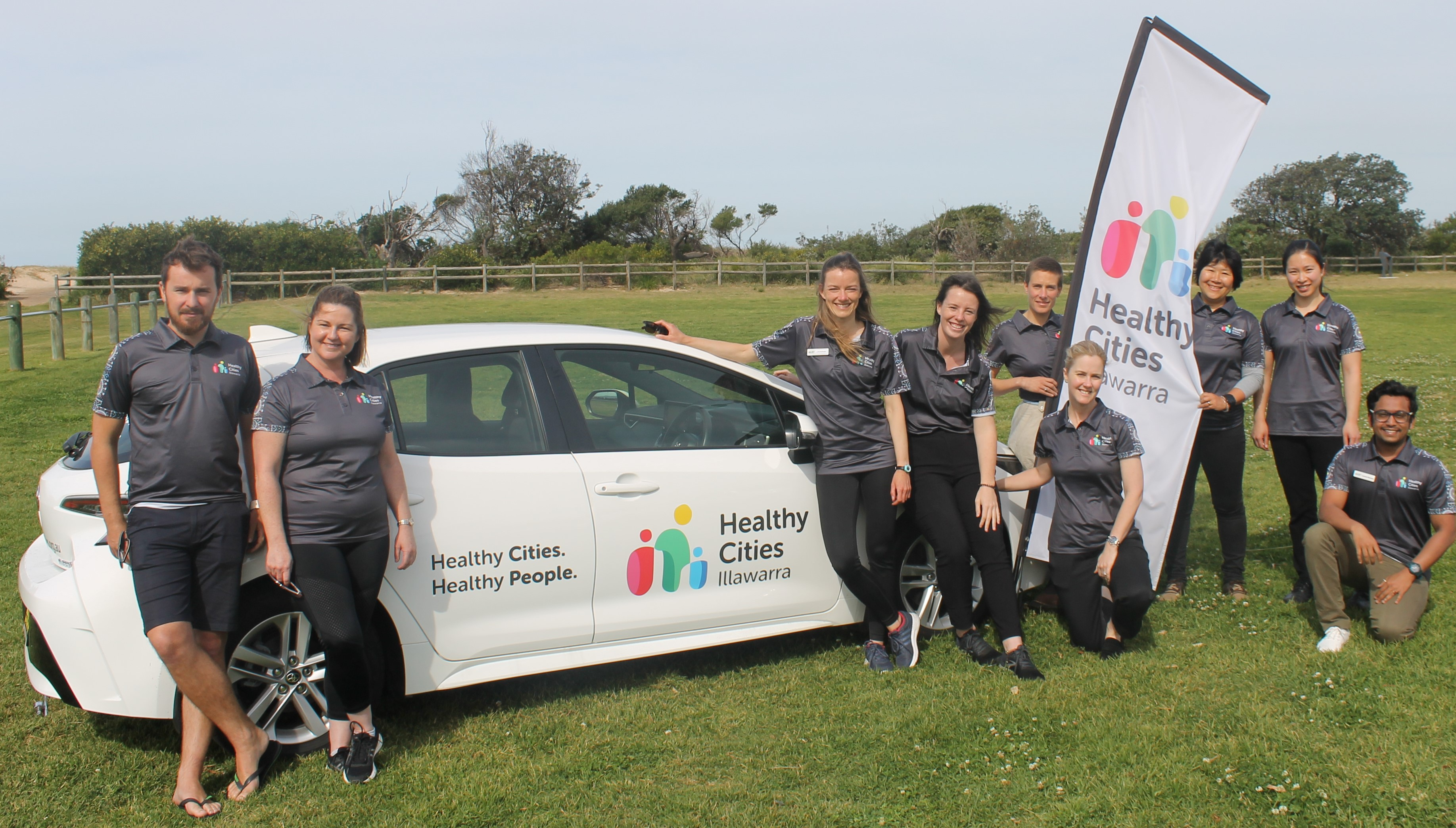 Members of the Healthy Cities Illawarra team stand beside a car and banner featuring their group's name.