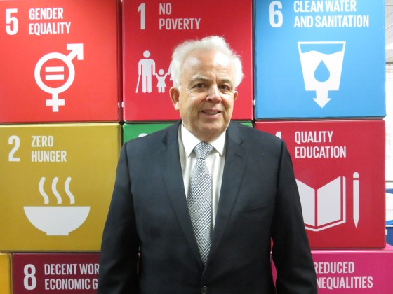 David Templeman stands in front of a board containing info graphics for some of the Sustainable Development Goals.